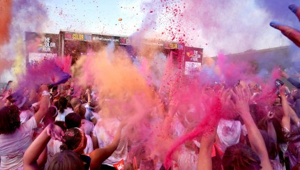 BRIGHTON, ENGLAND - SEPTEMBER 20:  Runners celebrate in the Festival Area after the Color Run presented by Dulux, known as the happiest 5km on the planet on September 20, 2014 in Brighton, England. Runners of all shapes, sizes and speeds start wearing white clothing. At each kilometre a different colour of powder is thrown in the air with the runners becoming a constantly evolving artwork. At the end of the course runners are greeted by the Color Festival where the air is filled with music and stunning coloured powder bursts creating a vibrant party atmosphere.  (Photo by Jordan Mansfield/Getty Images for Dulux)